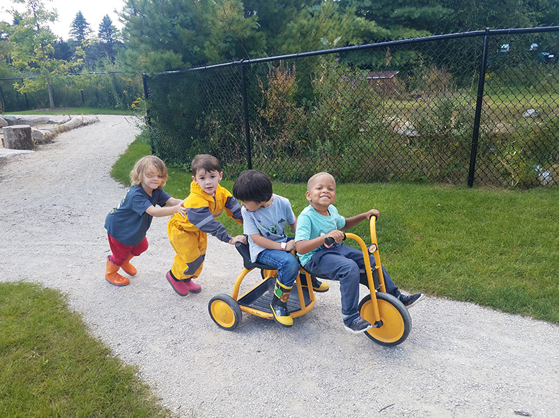 children pushing tricycle together