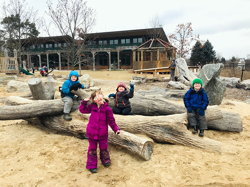 children playing on log feature