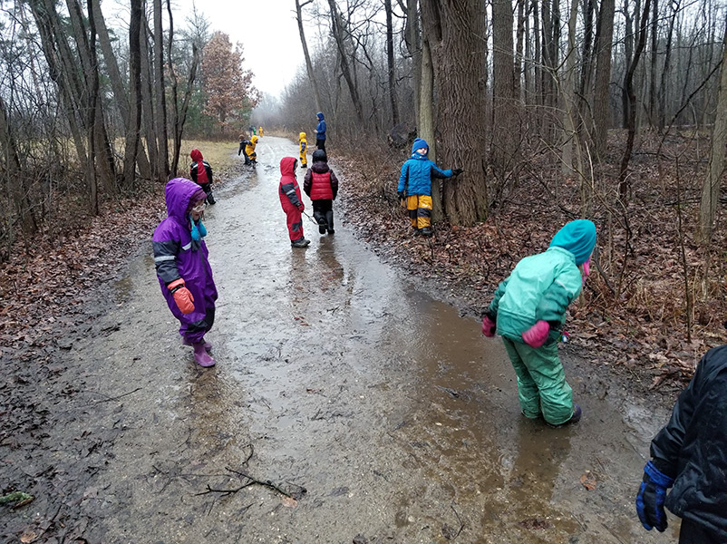 children in rainsuits playing on muddy trail