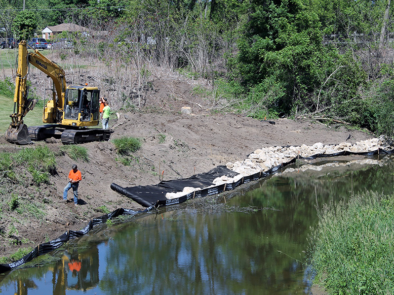 Restoring and stabilizing stream bank with heavy equipment
