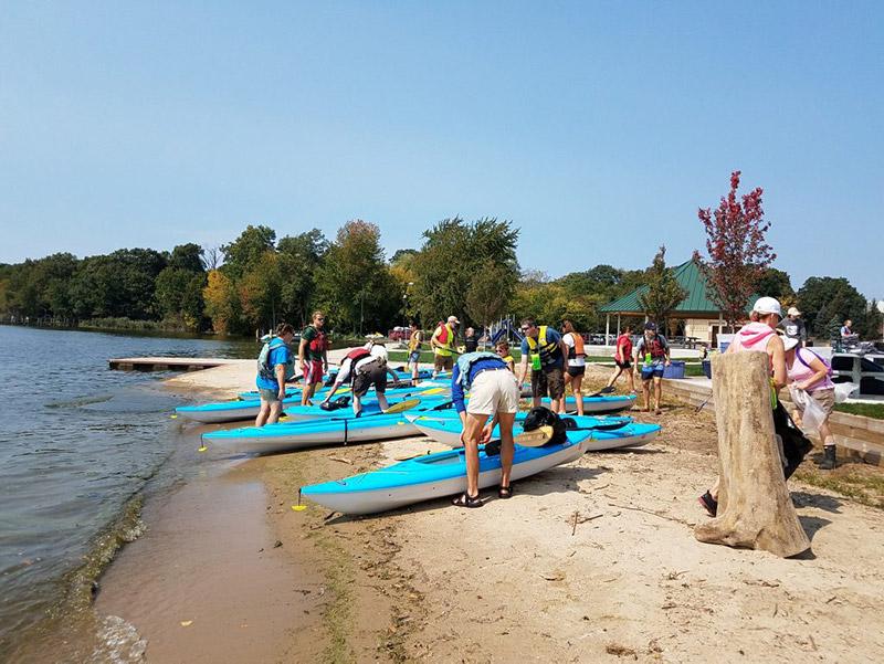 People launching kayaks into Lake Macatawa
