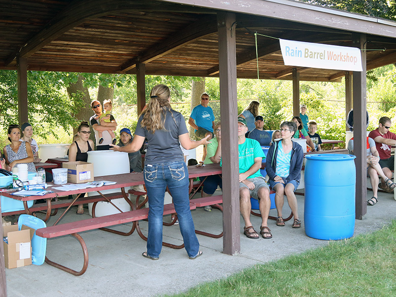 Teacher leading rain barrel workshop under pavillion