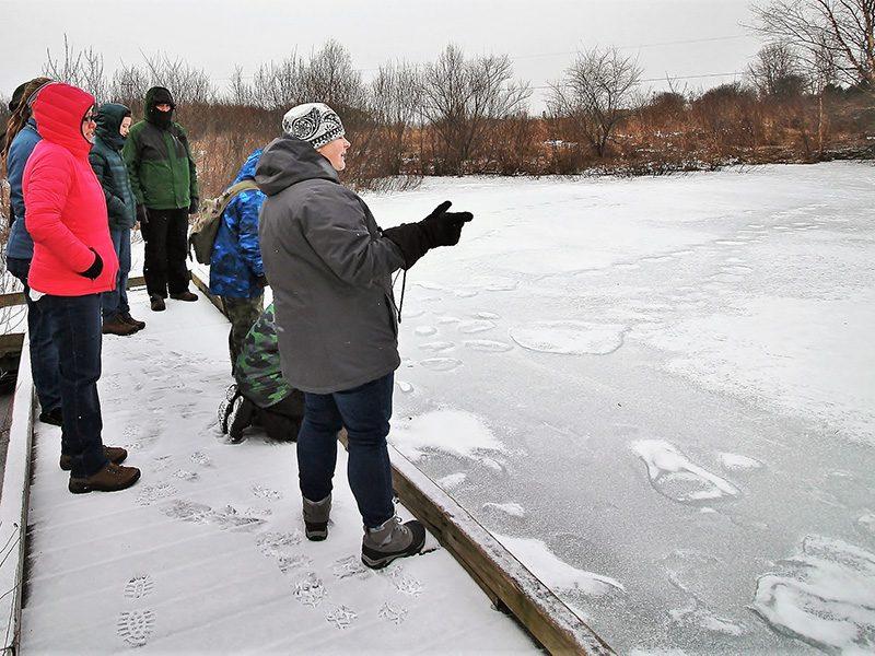 Naturalist educating participants near frozen pond