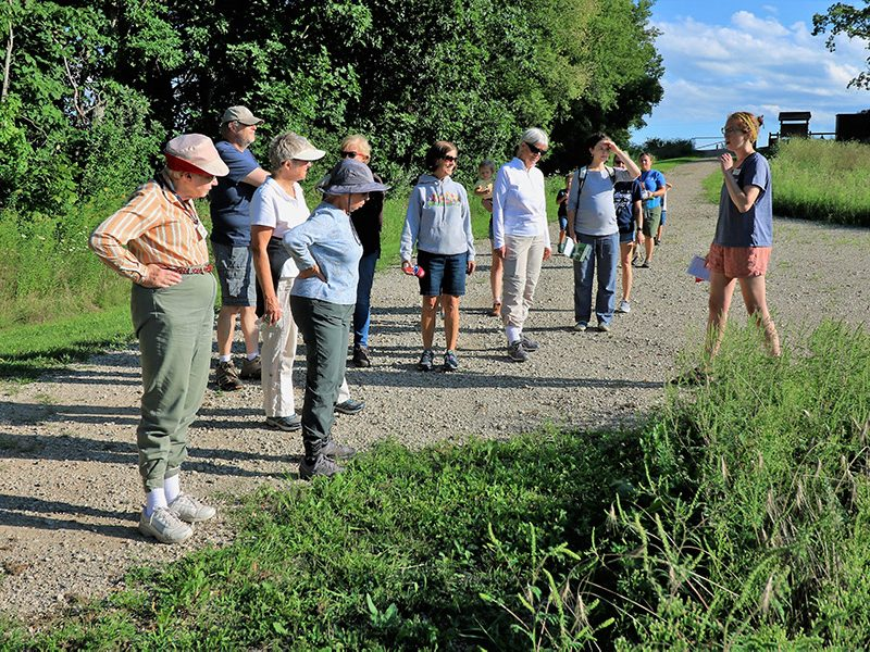 Naturalist leading a guided nature hike through along trail