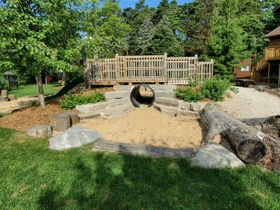 Natural play area with bridge and sandbox